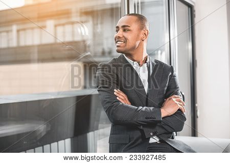 Young Respectable Businessman Sitting Near Window Of Office. He Looking With Happily Smile At Street