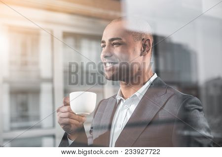 Waist Up Portrait Of Respectable Guy Is On The Other Side Glass. He Looking Into The Distance With S