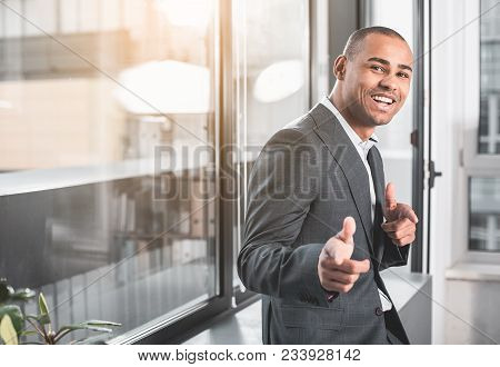 Waist Up Portrait Of African Respectable Man Standng Near Window With Wide Happily Smile On Face. He