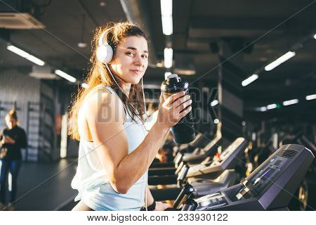 Sports Nutrition And Exercise. Beautiful Woman Holds Protein In Her Hand In Bottles, Shaker, Listens