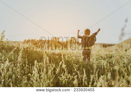 Cheerful Little Boy Running With His Back To Camera Along Sunlit Meadow. Copy Space In Left Side. Fu