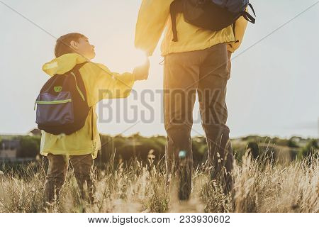 Glad Boy With Backpack Standing On Sunlit Grassland And Holding His Father By Hand