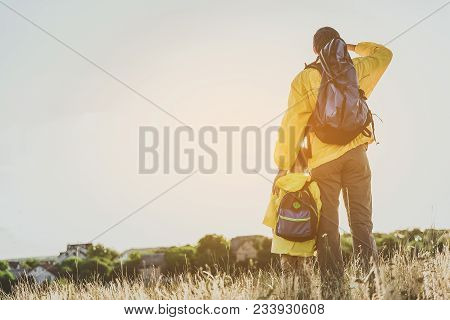 Adult Male And Boy With Backpack Standing On Sunlit Field With Their Backs To Camera And Peering Int