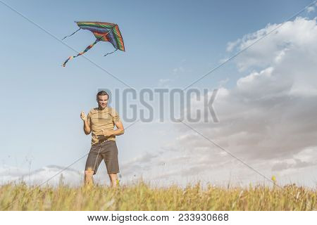 Glad Adult Man Standing On Sunlit Field, Colorful Kite Flying In Air Above Him. Copy Space In Right
