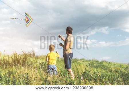 Adult Male And His Little Son Are Standing On Grassland And Flying A Kite. Copy Space In Right Side