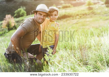 Portrait Of Happy Adult Man On Beautiful Sunlit Meadow Embracing Little Cheery Boy And Looking At Ca
