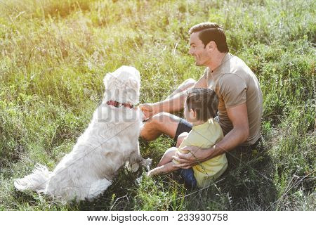Caring Joyful Father Sitting With His Little Son And Dog On Green Sunlit Meadow