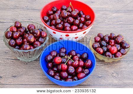 Berries Of A Sweet Cherry On A Wooden Background In A Plastic Cup. Ripe Red Sweet Cherry.
