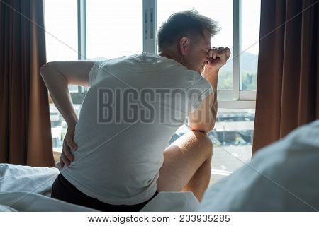 Young Man Wearing White T-shirt Sitting Indoor On The Bed Feeling Sudden Ache In His Back, Suffering