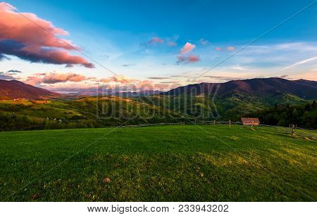 Gorgeous Mountainous Countryside At Dusk. Beautiful Landscape With Rural Fields, Fence And  Woodshed