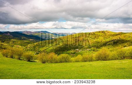 Lovely Rural Scenery In Mountains. Grassy Meadows Under The Cloudy Sky On A Bright Day. Village On A
