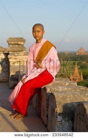 Bagan, Myanma - December 24, 2016: A Young Burmese Nun Girl Sits On The Parapet Of An Ancient Buddhi
