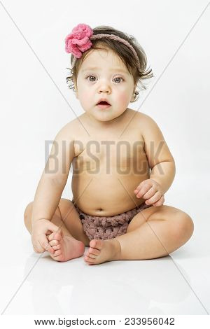 Cute Little Baby Girl With Pink Bow Flower On Her Head. Kid Looks Into The Camera With Admiration. C