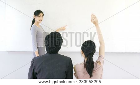 Asian Girl Points Hand On The Whiteboard Wall With The Student Sit On Front Of Classroom