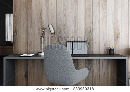 Interior Of A Modern Home Office With Wooden Walls, A Black Table With A Laptop On It And A Gray Arm