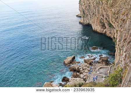 View From Above On The Sea And Stones Or Rocks In The City Of Taormina. The Island Of Sicily, Italy.