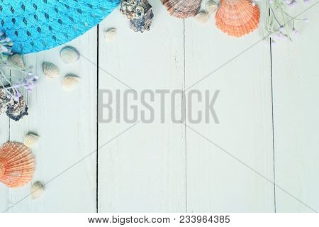 Beach Straw Hat And Seashells On A Wooden Background.photo With Place For Text.