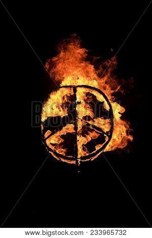 Burning peace symbol over black background