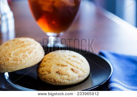 A Glass Of Iced Tea And Scones Or Biscuits On A Plate In A Restaurant
