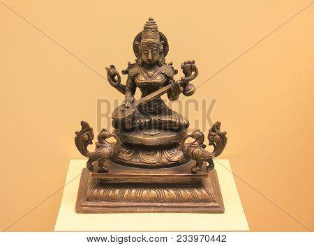 Saraswati Metal Statue Isolated. Saraswati Is Hindu Goddess Of Knowledge, Music, Art, Wisdom And Lea