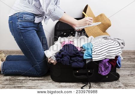 Young Girl Casually Packs Black Suitcase. Packing List In White Notebook