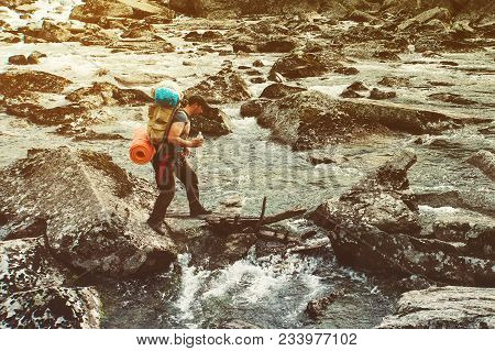 Hiker Man With Backpack Crossing A River. Hiking And Leisure Theme. Man Crosses A Mountain River Wit