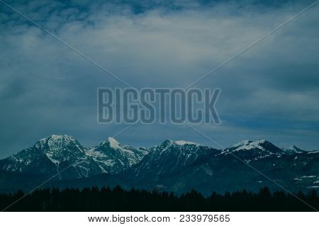 Photo Depicting A Beautiful Moody Frosty Landscape. European Alpine Mountains With Snow Peaks On A B