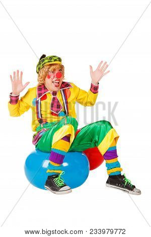Funny Clown Sits On Blue Ball Isolated On The White Background