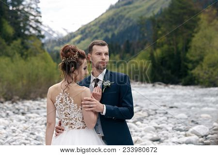 Wedding Walk. The Bride And Groom Walk Along The River Bank, Holding Each Other's Hands. Portrait Of