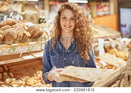 Young Attractive Female Model With Appealing Appearance Stands In Bakery Department, Chooses Bread O