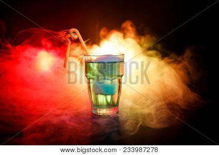 Alcohol Cocktail In Glass With Ice In Smoke On Dark Background. Club Drinks Concept. One Glass Of Co