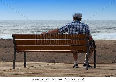 Pensioner Sitting On A Bench And Looking At Ocean