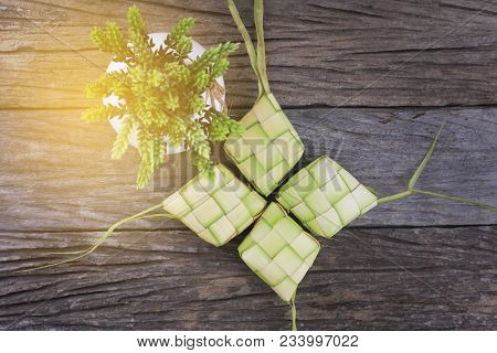 Ketupat (rice Dumpling) And Rice On Wood Background. Ketupat Is A Natural Rice Casing Made From Youn