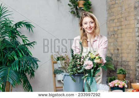 Image of florist woman in apron with bucket of flowers at table