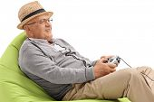 Senior sitting on a beanbag and playing video games isolated on white background poster