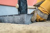 Workman installing paving stones or bricks in a close up view of his gloved hands holding a mallet to tamp them down onto a sand base in a low angle close up view. poster