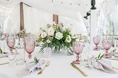 Beautiful table setting with crockery and flowers for a party, wedding reception or other festive event. Glassware and cutlery for catered event dinner poster