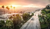 Aerial panoramic view of Ocean Ave freeway in Santa Monica beach at sunset - City streets of Los Angeles and California state surrounds - Warm twilight color filter tones with dark vignetting poster