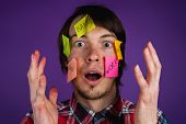 Portrait of a man with stickers on his face shocked by obligations, a man with his hands up in the face in shock from everyday routine, purple background poster