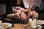 The snake in the hands of the witch and the fading candles on the table after fortune-telling and fortune-telling poster