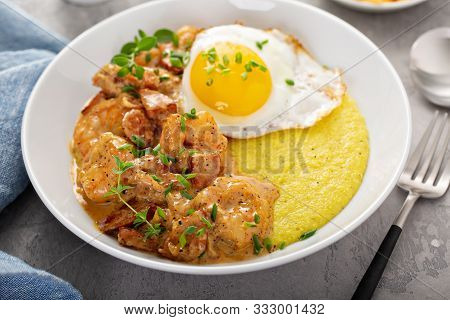 Shrimp And Cheesy Grits Topped With Egg Served For Breakfast