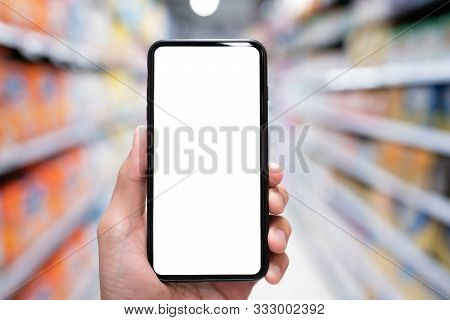 Hand Holding Mobile Smartphone Empty Touch Screen On Supermarket Or Convenience Stores Background.bl