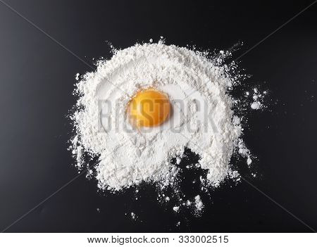 Flour And Egg Yolk On Black Background, Top View