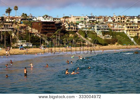 August 25, 2019 In Corona Del Mar, Ca:  People Swimming And Sunbathing At The Beach With Mansions On