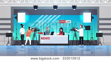 Male Presenter Interviewing Woman In Television Studio Tv Live News Show Video Camera Shooting Crew