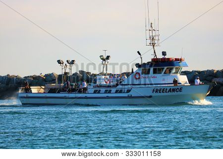 August 25, 2019 In Newport Harbor, Ca:  Fishing Vessel Riding Besides A Rock Jetty Riding Into Newpo