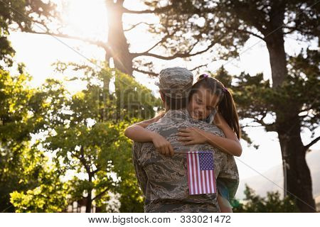 Rear view of a young adult mixed race male soldier in the garden outside his home, carrying his daughter, who is leaning over his shoulder holding a US flag and smiling with eyes closed