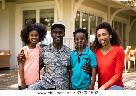 Portrait of a young adult African American male soldier in the garden outside his home, kneeling with his arms around his young son and daughter, his mixed race wife beside them, all smiling to camera poster