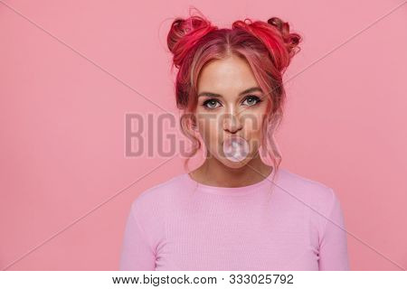 Portrait of attractive young woman in t-shirt with colored hair chewing gum isolated over pink background
