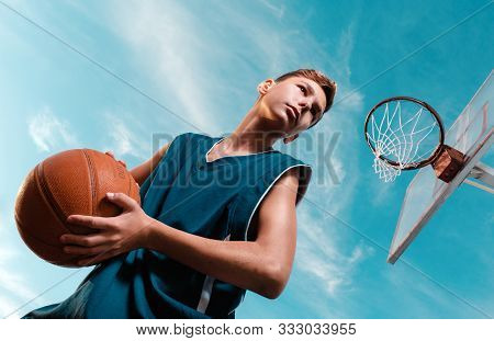 Sports And Basketball. A Young Teenager In A Black Tracksuit Stands With A Ball In His Hands And Pre